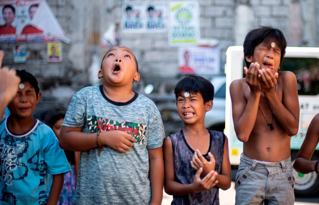 Boys contort their faces as they participate in a game where they need to slide a coin from their forehead to their mouth to win, during the annual Feast Day of St. Rita of Cascia in Manila, Philippines on May 19, 2019. (Photo by Noel Celis/AFP Photo)