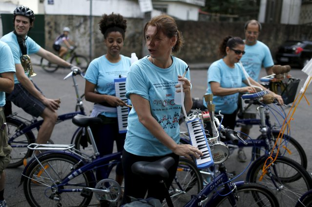 Members of the Cyclophonica band play instruments as they make a stop during a ride in Rio de Janeiro May 17, 2015. (Photo by Pilar Olivares/Reuters)