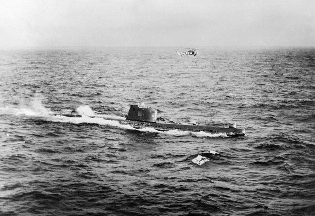 A Soviet submarine near the Cuban coast controlling the operations of withdrawal of the Russian Missiles from Cuba in accordance with the US-Soviet agreement, on November 10, 1962. American planes and helicopters flew at a low level to keep close check on the dismantling and loading operations, while US warships watched over Soviet freighters carrying missiles back to Soviet Union. (Photo by Getty Images)