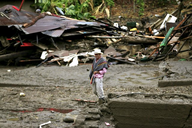 A resident stands in front a destroyed house, after a landslide sent mud and water crashing onto homes close to the municipality of Salgar in Antioquia department, Colombia May 19, 2015. (Photo by Jose Miguel Gomez/Reuters)