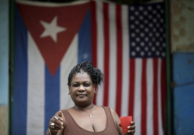 "Irma Diaz, 55, a housewife, poses for a photograph in front of the Cuban and U.S. flags in Havana, March 25, 2016. Regarding Obama's historic visit to the island, Diaz said ""I am happy with the friendship between Raul (Castro) and Obama"". Struggling under a U.S. embargo and still only cautiously emerging from a Soviet-style economy that prohibited almost all private enterprise, many Cubans find it hard to make ends meet. Residents of Havana hope that U.S. President Barack Obama's historic visit to Cuba last month will bring material improvements to their lives. (Photo by Ueslei Marcelino/Reuters)"