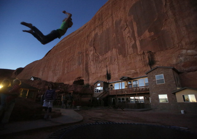 "Girls play on a trampoline near a home blasted from a rock wall at the Rockland Ranch community outside Moab, Utah, November 2, 2012. The ""Rock"" as it is referred to by the approximately 100 people living there in about 15 families, was founded about 35 years ago on a sandstone formation near Canyonlands National Park. (Photo by Jim Urquhart/Reuters)"
