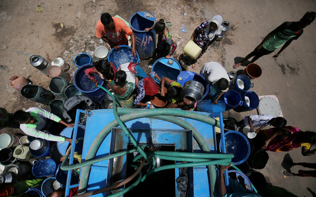 Local residents fill their empty containers with water from municipal corporation tanker on a hot summer day in Ahmedabad, India on May 20, 2019. (Photo by Amit Dave/Reuters)