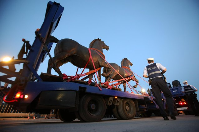 Two bronze horse statues by artist Josef Thorak are transported on a flatbed trailer in Bad Duerkheim, southwestern Germany, Thursday, May 21, 2015. A German investigation into black market art had recovered the two statues that once stood in front of Adolf Hitler's grand chancellery building in Berlin as well as other Nazi-era pieces that had been lost for decades. (Photo by Fredrik von Erichsen/dpa via AP Photo)