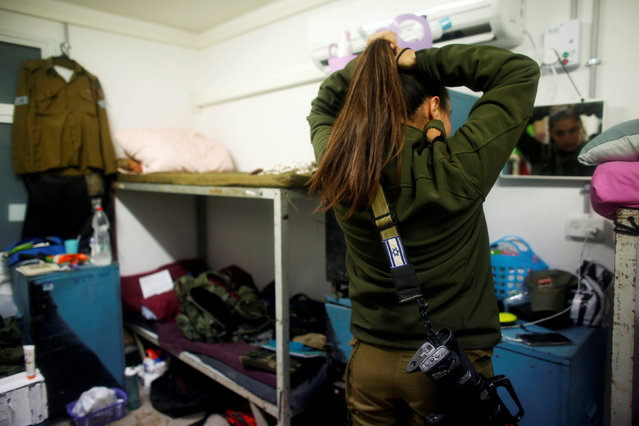 A female Israeli soldier from the Haraam artillery battalion fixes her hair in the women's living quarters at a military base in the Israeli-occupied Golan Heights March 1, 2017. (Photo by Nir Elias/Reuters)