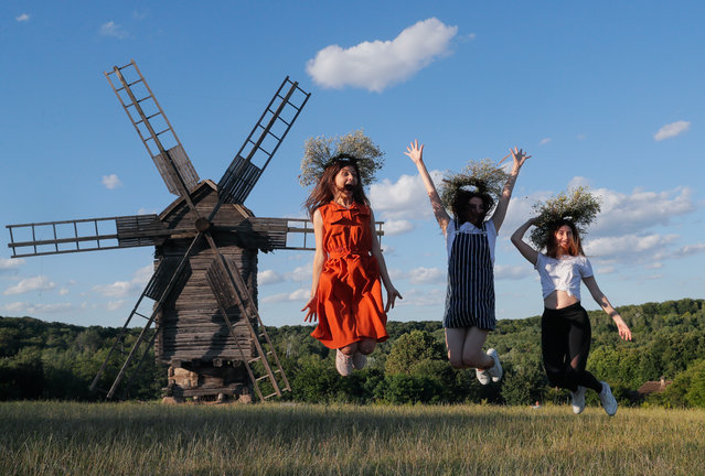 Ukrainian girls wearing flower's diadems jump in front of an old windmill in Kiev, Ukraine, 06 July 2019, as she celebrates the traditional pagan holiday of Ivana Kupala. Ivana Kupala is celebrated, during the summer solstice, on the shortest night of the year, marking the beginning of summer and is celebrated in Ukraine, Belarus, Poland and Russia. People sing and dance around bonfires, play games and perform traditional rituals. Young people jump over bonfires in order to test their bravery. Couples holding hands jump over the flames to test their love. If the couple does not succeed it is predicted to split up. Traditionally, children and young unmarried women wear wreaths of wild flowers on their heads to symbolize purity. (Photo by Sergey Dolzhenko/EPA/EFE)