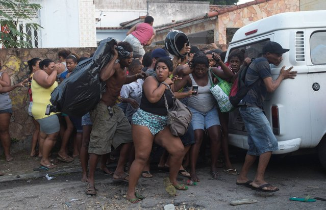 Squatters take cover from stun grenades and tear gas during an eviction in Rio de Janeiro, Brazil, Thursday, April 10, 2014. Squatters in Rio de Janeiro are clashing with police after a Brazilian court ordered that 5,000 people be evicted from abandoned buildings of a telecommunications company. Officers have used tear gas and stun grenades to try to disperse the families. (Photo by Silvia Izquierdo/AP Photo)