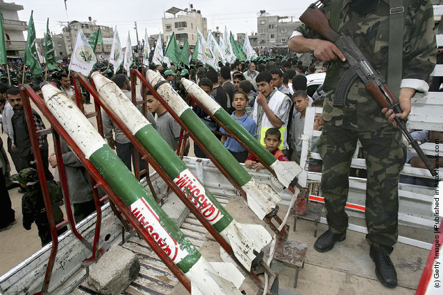 Masked Palestinian members of Al-Qassam Brigades the military wing of the Islamic Resistence Movement (HAMAS) show homemade Qassam Rockets