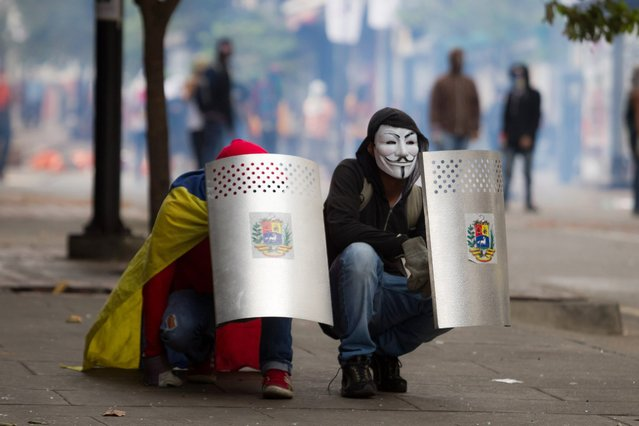 Opposition demonstrators try to take cover behind shields during clashes with police in Chacao, Caracas, April 16, 2014. Protests against Venezuelan President Nicolas Maduro's government have left 41 people dead and more than 650 injured, according to authorities. Maduro, the hand-picked successor to the late Venezuelan president Hugo Chavez, has accused demonstrators of trying to topple his government. (Photo by Miguel Gutierrez/EPA)