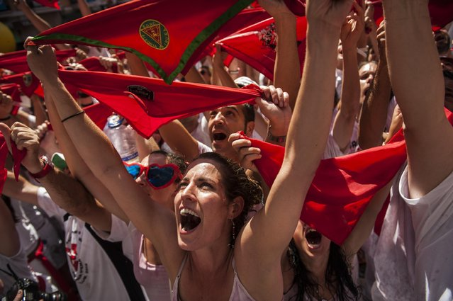 """Revelers celebrate during the launch of the """"Chupinazo"""" rocket, to celebrate the official opening of the 2015 San Fermin Fiestas, in Pamplona, northern Spain, Monday, July 6, 2015. Revelers from around the world kick off the festival with a messy party in the Pamplona town square, one day before the first of eight days of the running of the bulls glorified by Ernest Hemingway's 1926 novel """"The Sun Also Rises"""". (Photo by Alvaro Barrientos/AP Photo)"""