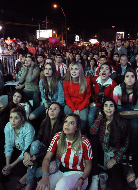 Fans of Paraguay's national soccer team react with dismay while watching the Copa America semifinal soccer match between Paraguay and Argentina, on a television screen in Asuncion, Paraguay, Tuesday, June 30, 2015. Argentina won the match 6-1. (Photo by Cesar Olmedo/AP Photo)