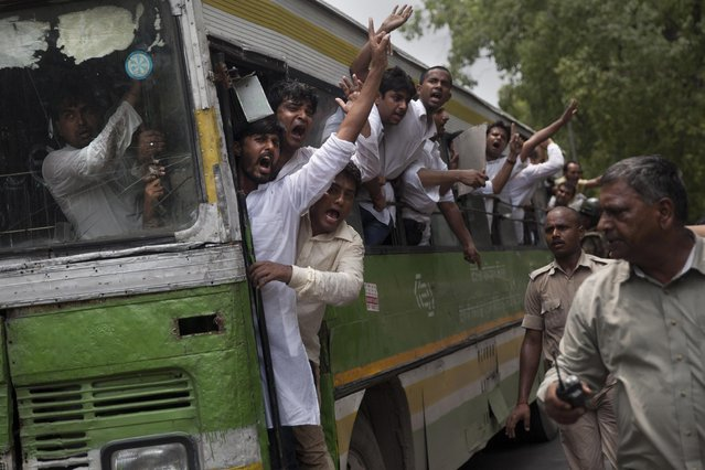 Activists of India's Congress party's youth wing shout slogans from a bus as they are detained during a protest against Shivraj Singh Chauhan, chief minister of the central Indian state of Madhya Pradesh, in New Delhi, India, Wednesday, July 8, 2015. (Photo by Tsering Topgyal/AP Photo)