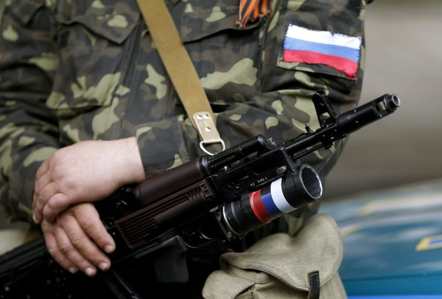 An armed pro-Russian activist holds his weapon as he stands near the seized regional government headquarters in Luhansk, eastern Ukraine, May 3, 2014. (Photo by Vasily Fedosenko/Reuters)