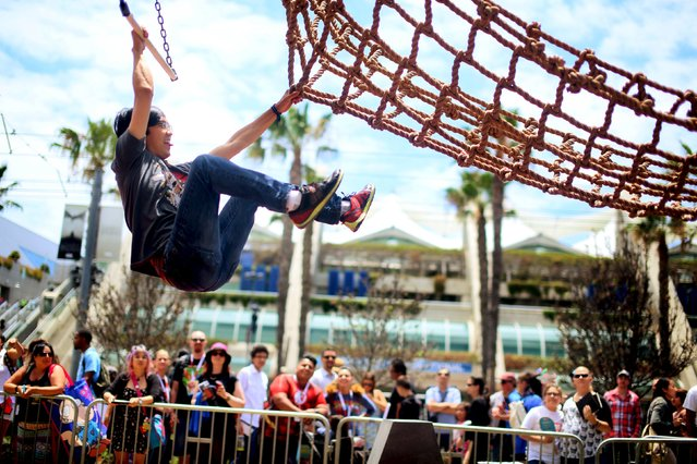 """Carlin Stella grabs onto netting while doing an obstacle course at the """"Assassins Creed Syndicate"""" booth outside of the 2015 Comic-Con International in San Diego, California July 10, 2015. (Photo by Sandy Huffaker/Reuters)"""