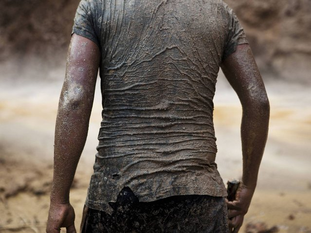 A miner continues his search for gold in mud-drenched clothes inside a crater at an illegal gold mine process in La Pampa in Peru's Madre de Dios region. The government claims that the informal miners have destroyed the surrounding forests and polluted the environment by using mercury in the gold extraction process. (Photo by Rodrigo Abd/AP Photo)