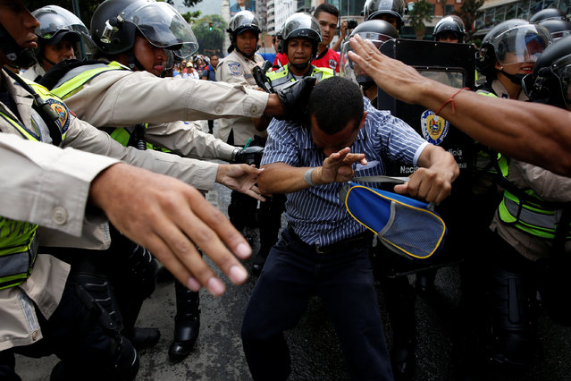 An opposition supporter clashes with riot policemen during a rally to demand a referendum to remove President Nicolas Maduro en Caracas, Venezuela, May 18, 2016. (Photo by Carlos Garcia Rawlins/Reuters)