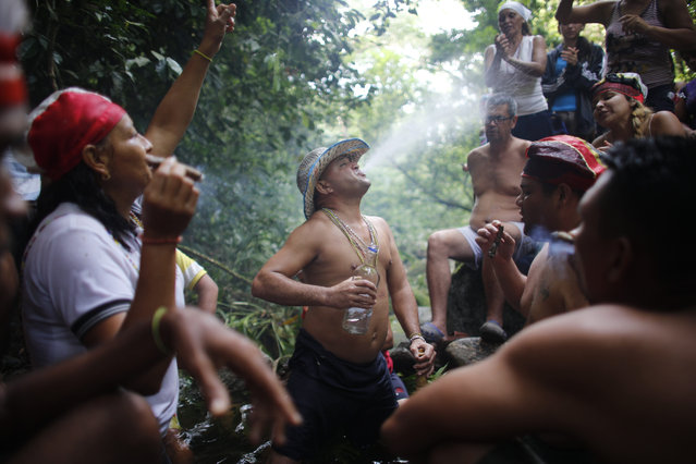 In this photo taken October 12, 2019, Juan Carlos Paso sprays water from his mouth on others during a ceremony on Sorte Mountain where followers of indigenous goddess Maria Lionza gather in Venezuela's Yaracuy state. The cult of the goddess is hundreds of years old and draws on elements of the Afro-Caribbean religion Santeria and indigenous rituals, as well as Catholicism. (Photo by Ariana Cubillos/AP Photo)