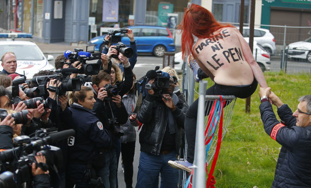 """A Femen activist is led away by police after activists lowered a banner protesting against Marine Le Pen's FN party in Henin-beaumont, northern France, Sunday, May 7, 2017. Voters across France are choosing a new president in an unusually tense and important election that could decide Europe's future, making a stark choice between pro-business progressive candidate Emmanuel Macron and far-right populist Marine Le Pen. The text on the activists' back reads """"Neither Marine Nor Le Pen"""". (Photo by Michel Spingler/AP Photo)"""