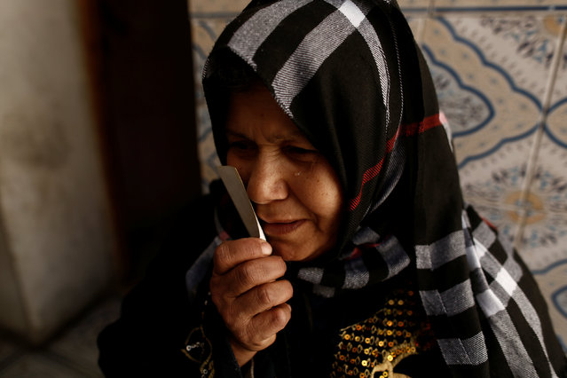 Fethiya Charni, weeps as she holds a photograph and the passport of her son Tarak Slimi, who is suspected to have joined Islamic State in Libya, at her house  in El Kef, Tunisia April 14, 2016. (Photo by Zohra Bensemra/Reuters)