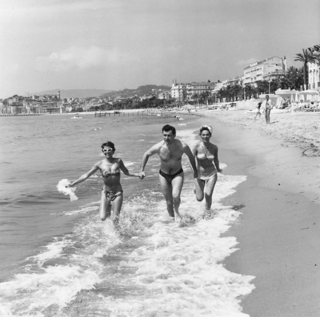 George Baker runs through the surf at Cannes with Bella Darvi and another young friend, 1956. (Photo by Haywood Magee/Picture Post/Getty Images)