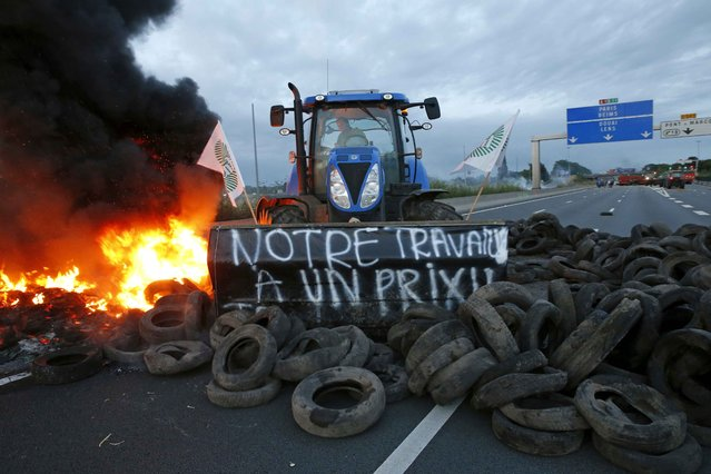"A French farmer pushes tyres onto fire with his tractor to block the A1 Lille-Paris highway early in the morning in Seclin, northern France, July 22, 2015. The placard reads ""Our work has a price"". (Photo by Pascal Rossignol/Reuters)"