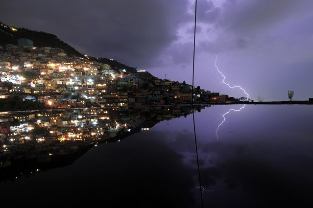 A long exposure shows lightning in the sky with reflection in the water on the floor of a building under construction during an evening thunderstorm on May 19, 2014 in the Haitian capital Port-au-Prince. (Photo by Hector Retamal/AFP Photo)