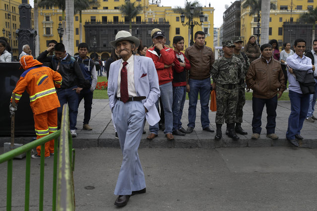 A man wearing a sky-blue suit listens to Peruvian President Ollanta Humala address onlookers in front of the government palace on Junin Street in Lima, Peru, Tuesday, July 28, 2015. President Humala delivered his last State of the Nation address to Congress as the nation celebrated 194 years as and independent country. (Photo by Martin Mejia/AP Photo)