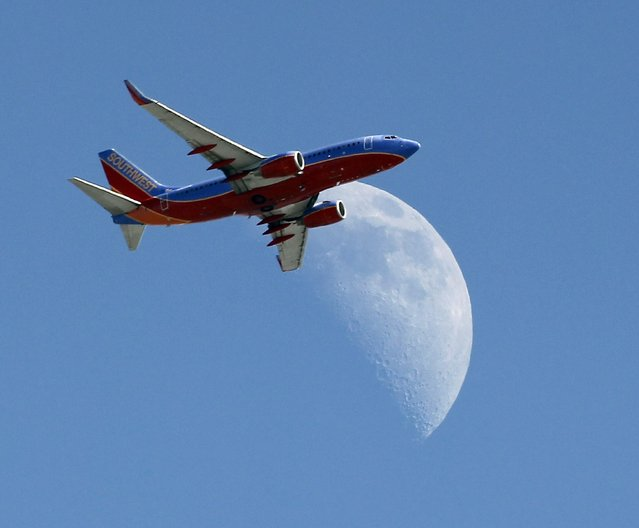 In this September 1, 2014 file photo, a Southwest Air flight   crosses over a crescent moon as it passes over Whittier, Calif. Southwest Air reports earnings later Thursday April 23, 2015. (Photo by Nick Ut/AP Photo)