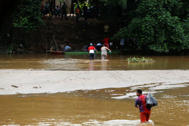A man crosses to Boca del Grita in Venezuela, carrying a plastic bag, through a river opposite the border town of Puerto Santander, Colombia, June 3, 2016. Picture taken from the Colombia side of the Venezuela-Colombia border. (Photo by Carlos Garcia Rawlins/Reuters)