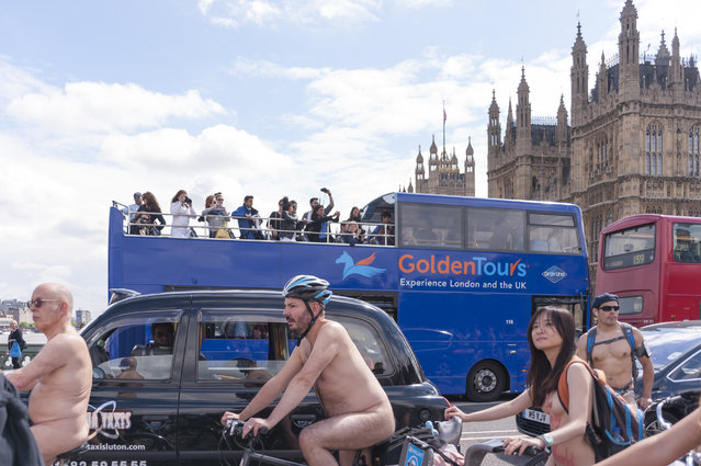 Tour bus patrons watch cycling activists take part in the annual World Naked Bike Ride in central London on June 14, 2014. The cyclists rode naked to protest against oil dependency and car culture, while raising awareness of cycling as an environmentally friendly option. (Photo by Stephen Chung/PA Images)
