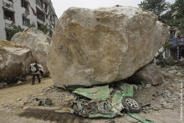 A survivor carrying goods evacuates the area past a huge rock lying on top of a car on a road near a mountain in the centre of earthquake-hit Beichuan county, Sichuan province, May 16, 2008