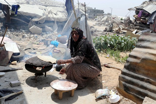 A Palestinian woman, whose house was destroyed by what witnesses said was Israeli shelling during a 50-day war last summer, bakes bread outside her makeshift shelter in Khan Younis in the southern Gaza Strip August 3, 2015. (Photo by Ibraheem Abu Mustafa/Reuters)