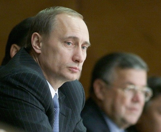 Russian Prime Minister Vladimir Putin watches the ice hockey match between Russia and Canada during the Baltika Cup tournament in Moscow, Thursday, December 16, 1999. Person at right is unidentified. (Photo by Mikhail Metzel/AP Photo)