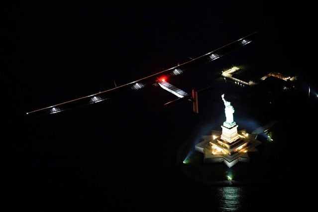 A handout picture obtained on June 11, 2016 from Solar Impulse 2 shows the Solar Impulse flying past the Statue of Liberty, as it approaches New York City for landing at Kennedy International Airport, with Andre Borshberg at the control. Andre Borschberg took off from Lehigh Valley to New York, the 14th leg of Round the World Journey and marks the final US leg. Departed from Abu Dhabi on march 9th 2015, the Round-the-World Solar Flight will take 500 flight hours and cover 35'000 km. (Photo by Jean Revillard/AFP Photo)