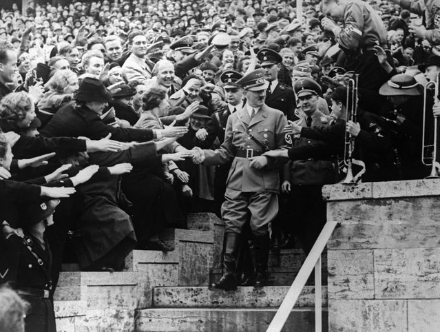 Nazi dictator Adolf Hitler (1889 - 1945) greets supporters at a May Day gathering in the Olympic Stadium, Berlin