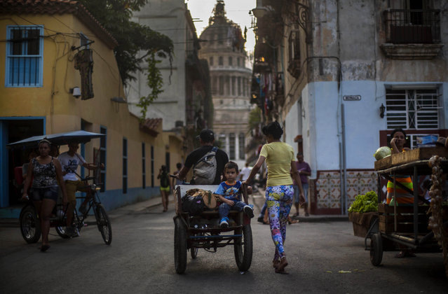 A child sits on the back of a moving bicycle cart, as a family member walks alongside the cart, near Capitolio in Havana, Cuba, Sunday, February 22, 2015. (Photo by Ramon Espinosa/AP Photo)