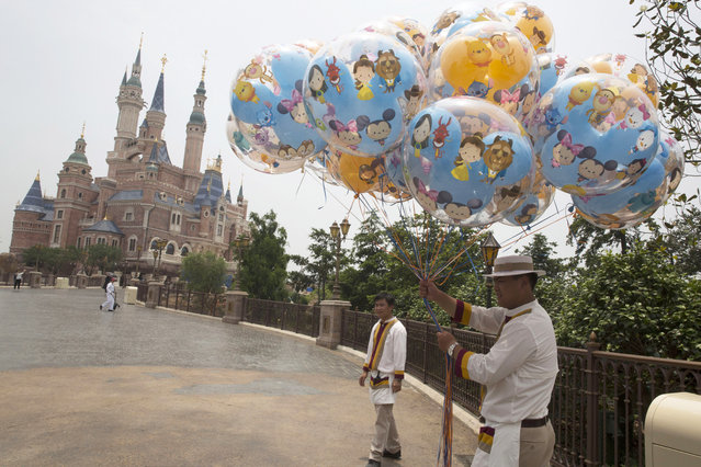 Workers prepare during the eve of the opening of the Disney Resort in Shanghai, China, Wednesday, June 15, 2016. (Photo by Ng Han Guan/AP Photo)