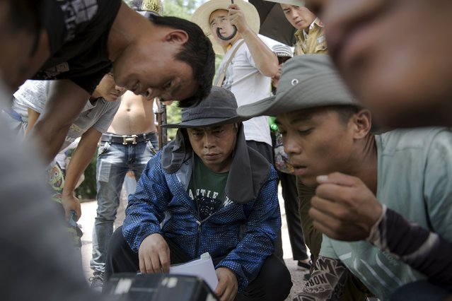 """The director (C) and his crew check recorded material as they shoot """"The Last Prince"""" television series on location near Hengdian World Studios near Hengdian July 24, 2015. (Photo by Damir Sagolj/Reuters)"""