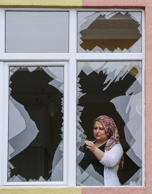 A woman takes a piece of glass from her shattered window, damaged after an attack on a nearby police station in Istanbul, Turkey, August 10, 2015. (Photo by Huseyin Aldemir/Reuters)