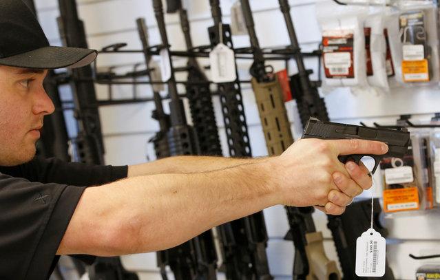 "Salesman Ryan Martinez dry fires a handgun at the ""Ready Gunner"" gun store in Provo, Utah, U.S., June 21, 2016. (Photo by George Frey/Reuters)"