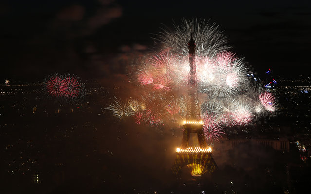 Bastille Day fireworks explode over the Seine river next to the Eiffel Tower in Paris Monday night, July 14, 2014. Bastille Day commemorates the storming by Parisians of the Bastille prison on July 14, 1789, setting off the French Revolution that toppled King Louis XVI and put an end to monarchy. (Photo by Jacques Brinon/AP Photo)