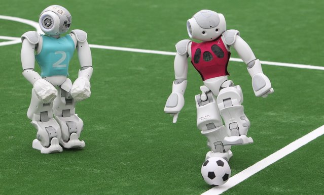 "Humanoid robots compete in a group match of the 20th RoboCup in Leipzig, Germany, June 30, 2016. Thousands of participants from over 40 countries are competing this year in RoboCup 2016 with their humanoid soccer playing robots in Leipzig, Germany. ""When established in 1997, the original mission was to field a team of robots capable of winning against the human soccer World Cup champions by 2050"", according to RoboCup. Now participants compete in five different soccer categories as well as RoboCup Rescue, which researches robotic effectiveness and usefulness to first responders. (Photo by Sebastian Willnow/EPA)"