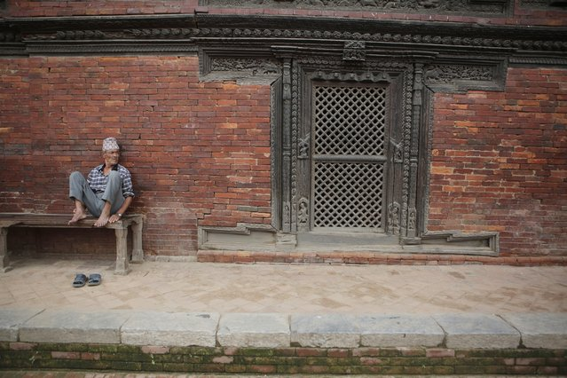 In this photo taken Friday, July 21, 2017, anelderly Nepalese man takes a rest at Patan Durbar Square in Lalitpur, Nepal. Centuries-old Char Narayan and Hari Shankara temples were completely destroyed by the massive April 2015 earthquake that shook the Himalayan nation, killing nearly 9,000 people. The temples were the jewel of the Patar Durbar Square, which is thronged by thousands of tourists and local visitors every day. The structures were crumpled by the force of the tremor and the carved doors, roof and brick structure lay in ruins. (Photo by Niranjan Shrestha/AP Photo)