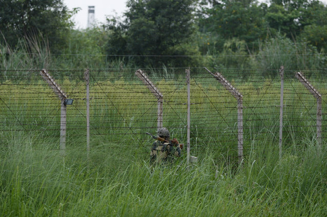 In this Sunday, August 9, 2015, photo, an Indian Border Security Force soldier patrols along the Pargwal area of India-Pakistan international border in Akhnoor,  sector 33 kilometers (21 miles) from Jammu, India. (Photo by Channi Anand/AP Photo)