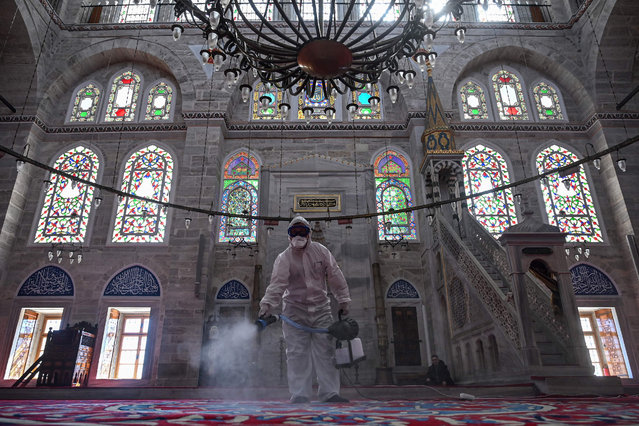 A member of Istanbul's Municipality disinfects the Mihrimah Sultan Mosque in Istanbul to prevent the spread of the COVID-19, the novel coronavirus, on March 13, 2020. Turkey said on March 12, 2020 it would shut all schools for two weeks and bar spectators from football matches through April after recording its first case of the new coronavirus.It followed a nearly six-hour cabinet meeting led by President Recep Tayyip Erdogan. (Photo by Ozan Kose/AFP Photo)