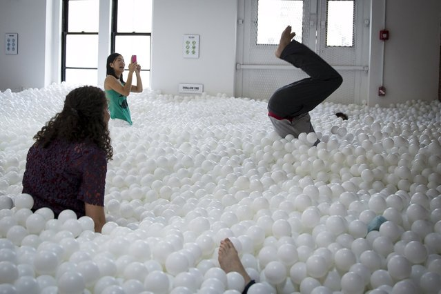 "A man does a flip into the ""JumpIn!"" ball pit, an interactive art installation by creative agency Pearlfisher made up of 81,000 white balls, in New York City August 25, 2015. (Photo by Mike Segar/Reuters)"