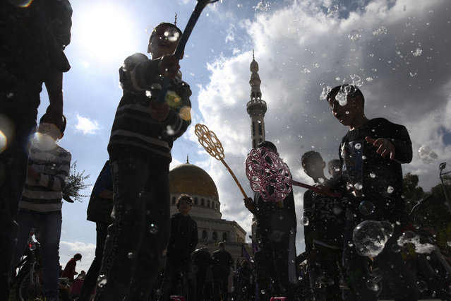 Israeli Arab kids play with soap bubbles during a protest against U.S. President Donald Trump's Mideast initiative, in the Israeli Arab town of Jaljulia, Israel, Friday, February 21, 2020. The proposal has infuriated many of Israel's Arab citizens, who view it as a form of forced transfer. (Photo by Oded Balilty/AP Photo)