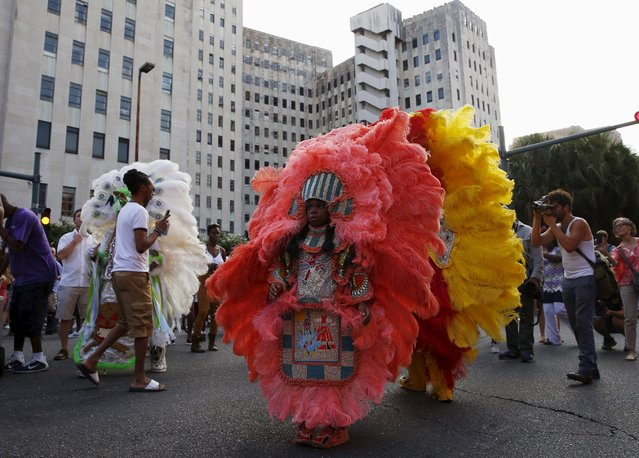 Members of the Creole Wild West Mardi Gras Indian Tribe parade past Charity Hospital, closed and vacant since Hurricane Katrina, in a second line parade to mark the tenth anniversary of the storm in New Orleans, Louisiana August 29, 2015. Creole Wild West is the oldest Mardi Gras Indian Tribe in the city. (Photo by Edmund D. Fountain/Reuters)