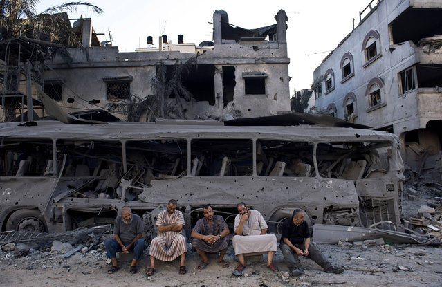 Five Palestinian men sit on August 20, 2014 next to a destroyed bus and houses in front of a house that was completely demolished after it was targeted by Israeli airstrikes late on August 19. Hamas said on August 20 that an Israeli air strike killed the wife and child of its Gaza military chief, as a temporary ceasefire went up in smoke and Cairo truce talks froze. (Photo by Roberto Schmidt/AFP Photo)