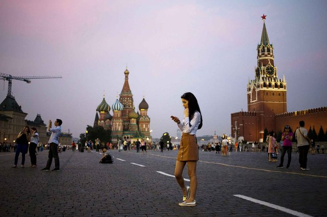 A young woman holds her smartphone at Red Square with the Kremlin's Spasskaya Tower, right, and St. Basil Cathedral, center, in the background in Moscow, Russia, Monday, July 25, 2016. (Photo by Pavel Golovkin/AP Photo)